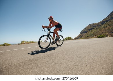 Image of young woman cycling on the country road. Fit female athlete riding down hill on bicycle. Woman doing cycling training.
