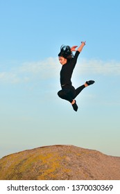 image of young woman doing gymnastic jump on a rock against a blue sky