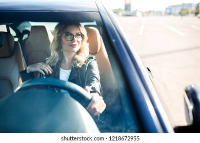 Image of young woman with glasses driving black car