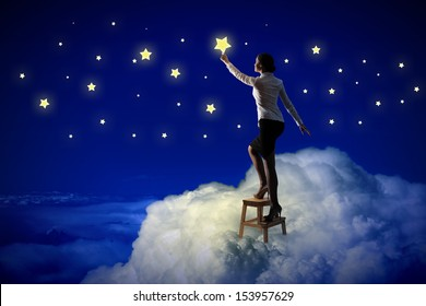Image of young woman lighting stars in night sky