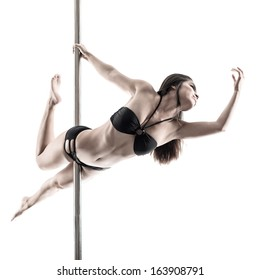Image of a young woman in lingerie exercising pole dance in the studio over white