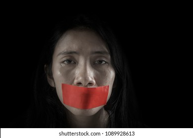 Image of young woman looks cried with her mouth covered by adhesive tape