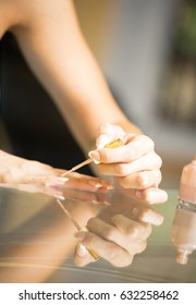 Image of young woman making manicure
