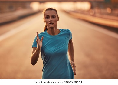Image of a young woman running hard on the road.