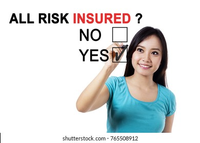 Image of young woman smiling at the camera and using a pen while choosing a yes option on the whiteboard with text of all risk insured