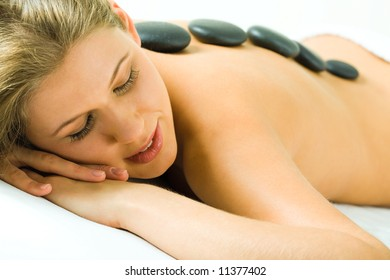 Image of young woman with spa stones sleeping