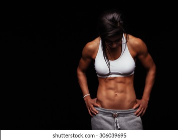 Image of young woman in sports clothing looking down against black background with copyspace. Muscular build female after workout.