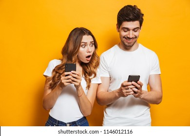 Image of young woman spying and peeking at smartphone of her boyfriend isolated over yellow background