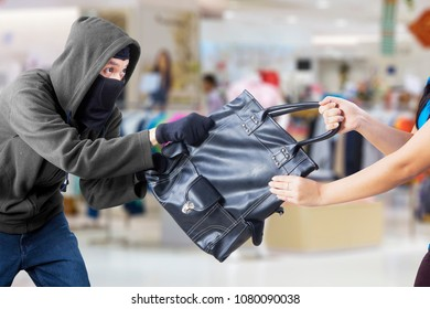 Image of young woman trying to protect her handbag from thief in the department store