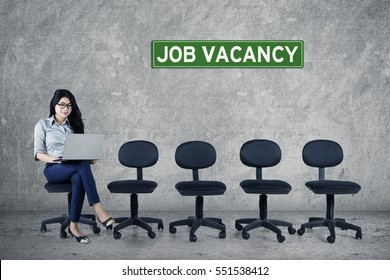 Image of young woman using a laptop while sitting on a chair with text of job vacancy on signboard and empty chairs