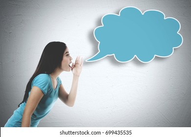 Image of young woman wearing casual clothes while whispering to an empty cloud
