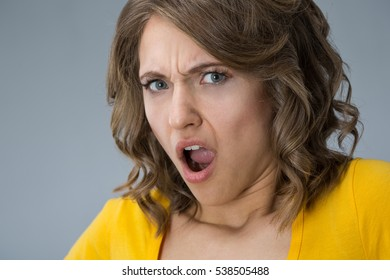 Image of young woman wearing yellow shirt and jeans shorts  make faces over grey background