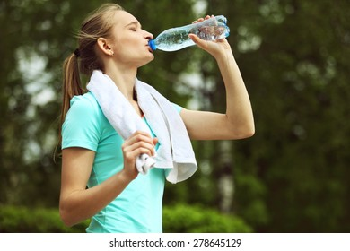 Image of young woman with white towel on her neck drinking water
