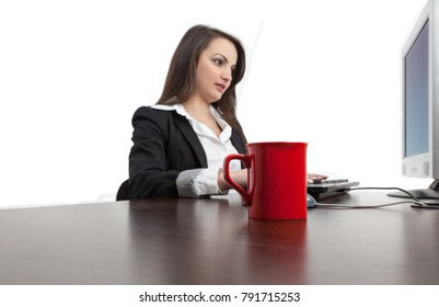 Image of a young woman working on a computer with a red cup of coffee on her desk.Selective focus on the red cup.