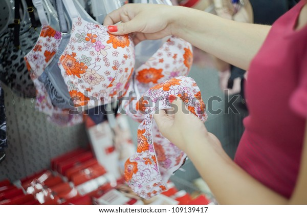 Image of a young woman's hands who chooses underwear in the supermarket.