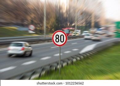 Image with zoom effect showing 80 km/h speed limit traffic sign on a highway full of cars
