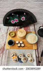 Imagen tomada a cuarenta y cinco grados de platos de sushi con abanico negro, ginseng y wasabi, salsa de soja, tablero de bambú, uramaki y california roll