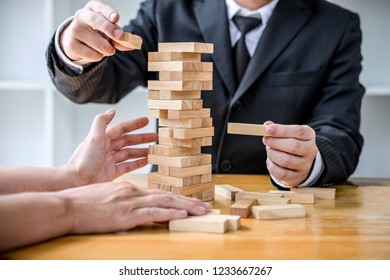 Images of hand of businesspeople placing and pulling wood block on the tower, Alternative risk concept, plan and strategy in business, Risk To Make Business Growth Concept With Wooden Blocks.