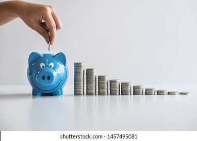 Images of stacking coins and Hand putting coin into blue piggy bank for planning step up to growing and savings with money box, Saving money for future plan and retirement fund concept.