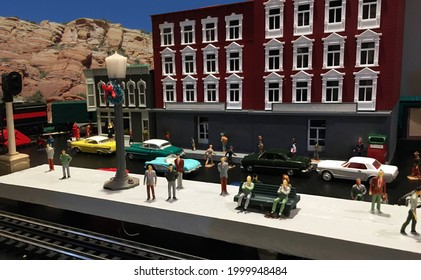 Imaginary comuters waiting for a train in an imaginary town on a train board