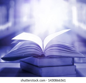 Imagine opening a magic book with bright white light and softness on a wooden table with a blurred bookshelf. Fantasy magic For wallpapers, beautiful computer screen wallpapers
