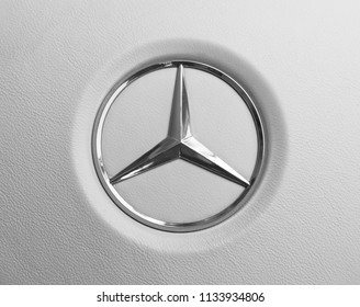 Imatra, Finland, September 3 2017: Close up view of a Mercedes-Benz logo on white leather steering wheel. Modern car interior details. Black and white