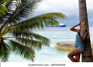 An Imave of Beautiful Girl Looking at the Ocean, Bandos, Maldives. Focus over the Palm Leaves.