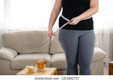 imbalanced nutrition, weight gain, dieting. overweight woman with french fries, chips and measuring tape