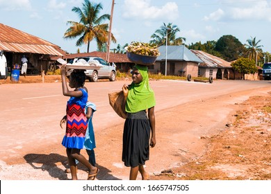 Imiakebu, Edo/Nigeria - november 01, 2019: little african children carrying products on their head, returning from a farm, selling along the street