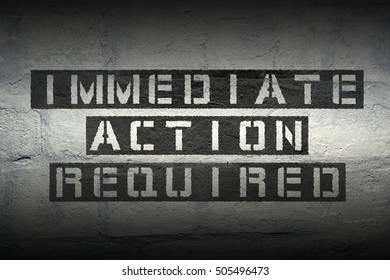 immediate action required exclamation stencil print on the grunge white brick wall