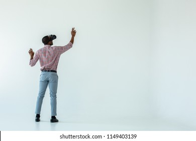 Immensive device. Full length of a professional afro american man standing against white background while wearing VR glasses