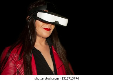 Immersive augmented reality, woman smiling  with long brown hair red jacket living augmented reality experience with special glasses to observe in Mexico