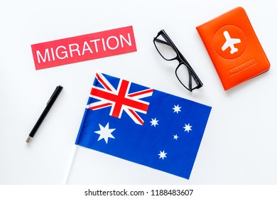 Immigration to Australia concept. Text immigration near passport cover and australian flag on white background top view