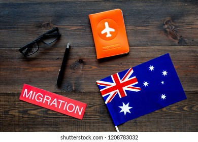 Immigration to Australia concept. Text immigration near passport cover and australian flag on dark wooden background top view