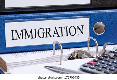 Immigration - blue binder on desk with calculator and pen