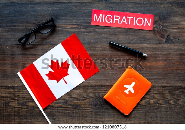 Immigration to Canada concept. Text immigration near passport cover and canadian flag on dark wooden background top view space for text
