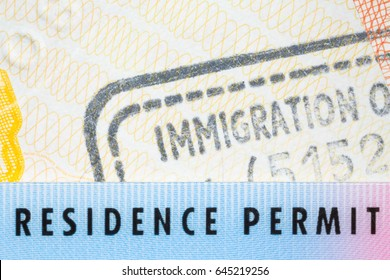 Immigration concept image. Residence permit card over immigration stamp on UK visa in passport. Selective focus