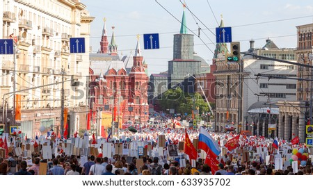 Immortal Regiment procession in Victory Day-thousands of people marching along Moskva River embankment towardn the skyscraper of the Stalin era with flags and portraits of soldiers of World War Two