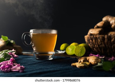 Immune boosting ginger and lemon tea with steam coming out of the cup and a basket full of ginger roots, lime, peppermint leaves and pink flowers. Black background with copy space.