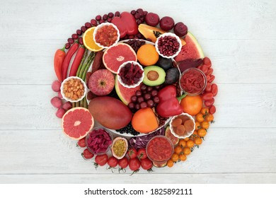 Immune boosting health food high in lycopene, anthocyanins, antioxidants, vitamins, minerals & dietary fibre. With fruit & vegetables in a circular design on a plate & loose on rustic wood.