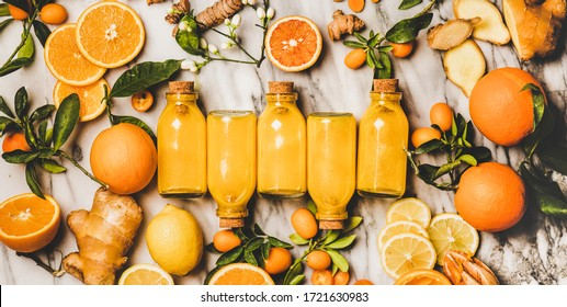 Immune boosting vitamin health defending drink. Flat-lay of fresh turmeric, ginger, citrus juice shot in glass bottles over marble background, top view. Pure vegan Immunity system booster