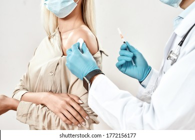 Immunisation. Cropped close up shot of male doctor in blue sterile gloves injecting vaccine to a young woman wearing medical mask. Vaccination, medicine and healthcare. Covid, coronavirus vaccine