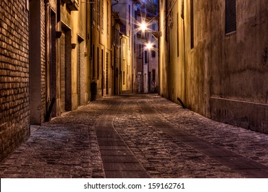 Imola, Bologna, Emilia Romagna, Italy: narrow dark alley in the old town - street at night in the Italian city