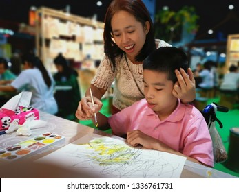 Impact Muang Thong, Bangkok, Thailand - MAR 08, 2019: Disabled child on the wheelchair is excited to draw with other people in the art exhibition with his mother, She encouraged her son.