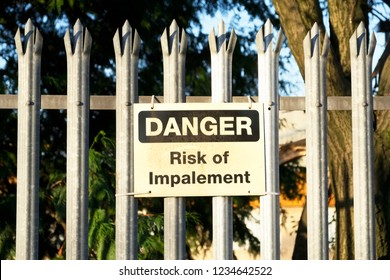 Impalement danger and risk sign on fence for security and protection