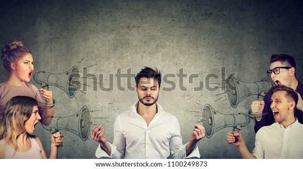 Impassive meditierende junge Geschäftsleute ohne Rücksicht auf die Menge des Schreiens in Megaphone wütende Menschen