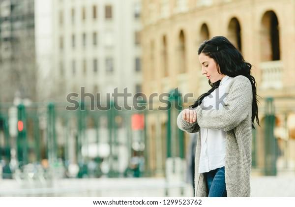 Impatient girlfriend waiting for her boyfriend at a train station.