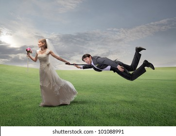Impatient happy wife pulling her husband by his arm and running on a green meadow