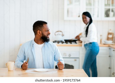 Impatient Hungry Black Husband Waiting For Food, Sitting At Table In Kitchen With Angry Face Expression, Annoyed Man Complaining About Empty Plate While His Spouse Cooking Lunch On Background