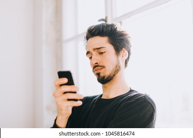 Impatient mediterranean man looks at cellphone